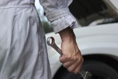 Schließen Sie herauf Hände des professionellen jungen Mechanikermannes, der Schlüssel gegen Auto in der offenen Haube an der Repa Stockfotografie