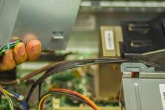 Schließen Sie herauf Hände des Technikers während des Tischrechners der Reparatur Stockfoto