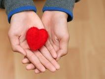 Schließen Sie herauf Hände ein rotes Herz der Mannholding und -person auf hölzerner Tabelle Lizenzfreie Stockbilder