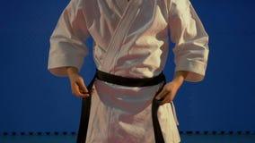 Schließen Sie herauf Hände eines Mannes, der auf den schwarzen Gürtel auf seinem weißen Karatekimono in Zeitlupe sich setzt stock video footage