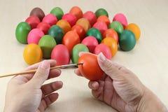 Schließen Sie herauf Hände von bunten Eiern der christlichen Malerei gegen den Malerpinsel, der für Ostern-Feiertag auf Marmorpla lizenzfreie stockfotos