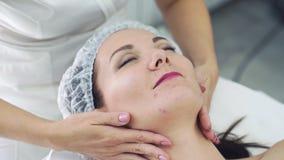 Schließen Sie herauf Hände von Cosmetologist im Schönheitssalon, der Gesichtsmassage Frau mit geschlossenen Augen antut stock footage