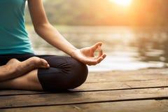 Schließen Sie herauf Hand Frau tun yoda das im Freien Frau, die Yoga am Naturhintergrund ausübt Lizenzfreie Stockbilder