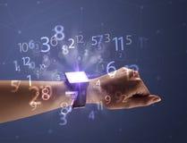 Schließen Sie herauf Hand mit smartwatch und Zahlen Lizenzfreie Stockfotos