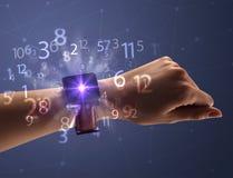 Schließen Sie herauf Hand mit smartwatch und Zahlen Stockfotos