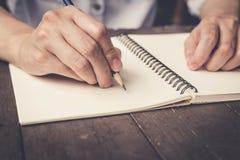 Schließen Sie herauf Handfrauen-Schreibensnotizbuch auf hölzernem Tabellenhintergrund Stockbilder