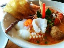 Schließen Sie herauf heißen würzigen Meeresfrüchtenudelkalmar, Garnele, Fischball, und Eier onsen mit Suppe auf der weißen Schüss Stockfotografie