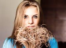 Schließen Sie herauf junge blonde Schönheitsfrau mit Blumen auf einem dunklen Hintergrund Mode-blondes vorbildliches Porträt Lizenzfreies Stockbild