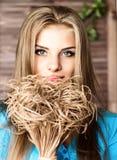 Schließen Sie herauf junge blonde Schönheitsfrau mit Blumen auf einem dunklen Hintergrund Mode-blondes vorbildliches Porträt Stockfotografie