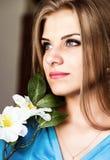 Schließen Sie herauf junge blonde Schönheitsfrau mit Blumen auf einem dunklen Hintergrund Mode-blondes vorbildliches Porträt Lizenzfreie Stockbilder