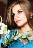 Schließen Sie herauf junge blonde Schönheitsfrau mit Blumen auf einem dunklen Hintergrund Mode-blondes vorbildliches Porträt Stockfoto
