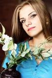Schließen Sie herauf junge blonde Schönheitsfrau mit Blumen auf einem dunklen Hintergrund Mode-blondes vorbildliches Porträt Stockfotos