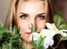 Schließen Sie herauf junge blonde Schönheitsfrau mit Blumen auf einem dunklen Hintergrund Mode-blondes vorbildliches Porträt Lizenzfreies Stockfoto