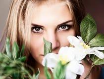 Schließen Sie herauf junge blonde Schönheitsfrau mit Blumen auf einem dunklen Hintergrund Mode-blondes vorbildliches Porträt Stockbild