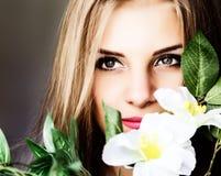 Schließen Sie herauf junge blonde Schönheitsfrau mit Blumen auf einem dunklen Hintergrund Mode-blondes vorbildliches Porträt Lizenzfreie Stockfotografie