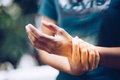 Schließen Sie herauf junge Frau A, die ihr schmerzliches Handgelenk hält Stockbild