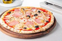 Schließen Sie herauf köstliche Fleisch-Pizza mit Speck, Hühnerleiste, Pilzen in Scheiben und Oliven auf dem hölzernen Brett auf d Stockfoto