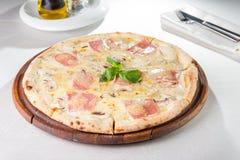 Schließen Sie herauf köstliche Pizza mit der Pilze in Scheiben und Frischkäse des Speckes, auf dem hölzernen Brett auf dem gedien Lizenzfreies Stockfoto