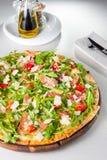 Schließen Sie herauf köstliche Pizza mit hamon und Kirschtomatenscheiben, parmezan Käse und Arugula auf dem hölzernen Brett auf t Lizenzfreies Stockbild