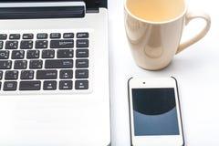 Schließen Sie herauf Kaffeetasse mit dem Laptop und Handy, die auf Weiß lokalisiert werden Stockfotografie