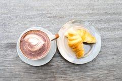 Schließen Sie herauf Kaffeetasse und Hörnchen stockfoto