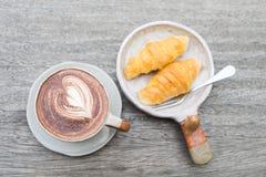 Schließen Sie herauf Kaffeetasse und Hörnchen stockbilder