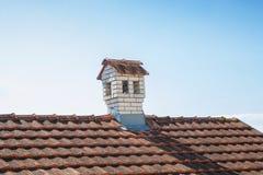 Schließen Sie herauf Kamin wie ein kleines Haus auf dem Dach Stockbild