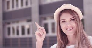 Schließen Sie herauf lächeln die recht junge Frau, die oben zeigt Lizenzfreies Stockfoto