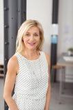 Schließen Sie herauf lächelnde blonde Frau innerhalb des Büros Lizenzfreie Stockbilder