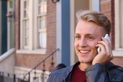 Schließen Sie herauf lächelnden attraktiven jungen Guy Talking zu jemand unter Verwendung des Handys Lizenzfreie Stockbilder