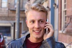 Schließen Sie herauf lächelnden attraktiven jungen Guy Talking zu jemand unter Verwendung des Handys Lizenzfreies Stockbild