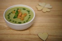 Schließen Sie herauf Lebensmittelphotographiebild der heißen gekochten grünen Gemüsesuppe mit Croutons und hölzernen Liebesherzde stockfoto