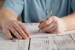 Schließen Sie herauf linke männliche ` s Handschrift auf dem Papier und unordentliches Mathe schreiben, Stockbild