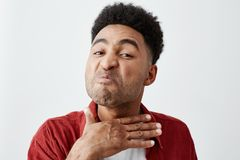 Schließen Sie herauf lokalisiertes Porträt des jungen dunkelhäutigen Mannes mit Afrofrisur im zufälligen weißen T-Shirt unter rot lizenzfreie stockbilder