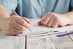 Schließen Sie herauf männliche ` s Handschrift auf dem Papier und unordentliches Mathe schreiben, stude Stockbild
