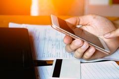 Schließen Sie herauf Mann unter Verwendung des Handys durch Karteninformationen wenn shoppi Lizenzfreie Stockbilder
