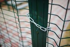 Schließen Sie herauf metallischen Netz-förmigen grünen Zaun, der geschlossen und durch Kette eingewickelt Lizenzfreie Stockfotos