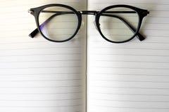 Schließen Sie herauf moderne Gläser auf unscharfem geöffnetem Buch mit Kopienraum lizenzfreie stockfotos