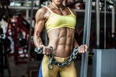 Schließen Sie herauf muskulöse Frau in der Sportkleidung, die Ketten in ha hält Stockfoto