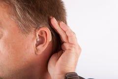 Schließen Sie herauf Ohr eines tragenden Hörgerätes des Mannes und des Hörens auf einen qu Stockfoto