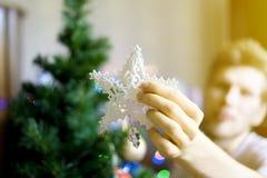 Schließen Sie herauf Person ` s Hände, die weißen Dekorationsstern auf christmass Baum f setzen stockfotografie