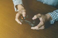 Schließen Sie herauf Person ` s Hand-playng Videospiel, das auf Holztischkonzept lokalisiert wird lizenzfreie stockfotos