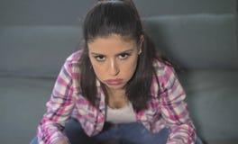 Schließen Sie herauf Porträt der jungen attraktiven und traurigen hispanischen Frau, welche zu Hause die Couch sitzt, die betont  stockfoto