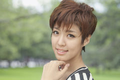 Schließen Sie herauf Porträt der jungen Frau mit dem kurzen Haar lächelnd, draußen lizenzfreie stockfotos