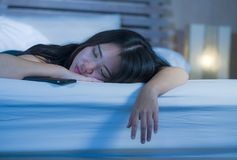 Schließen Sie herauf Porträt der jungen süßen und schönen asiatischen Chinesin 20s oder 30s, die im Bett nahe bei ihrem Handy im  Lizenzfreie Stockfotos