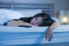 Schließen Sie herauf Porträt der jungen süßen und schönen asiatischen Chinesin 20s oder 30s, die im Bett nahe bei ihrem Handy im  Stockfotografie