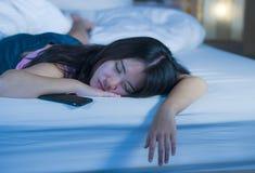 Schließen Sie herauf Porträt der jungen süßen und schönen asiatischen Chinesin 20s oder 30s, die im Bett nahe bei ihrem Handy im  Stockbilder