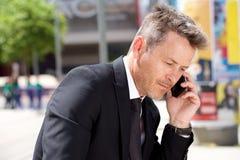 Schließen Sie herauf Porträt des ernsten Mannes in der Klage beim Geschäftsanruf draußen lizenzfreies stockfoto