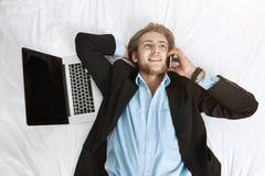 Schließen Sie herauf Porträt des frohen hübschen Geschäftsmannes, der auf Bett in der Klage mit Laptop und Handy liegt Unterhaltu Stockbild