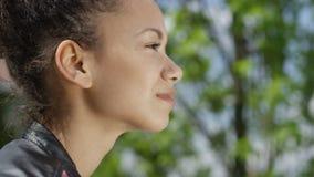 Schließen Sie herauf Porträt des jungen Afroamerikanermädchens, das im sonnigen Park sich entspannt stock video